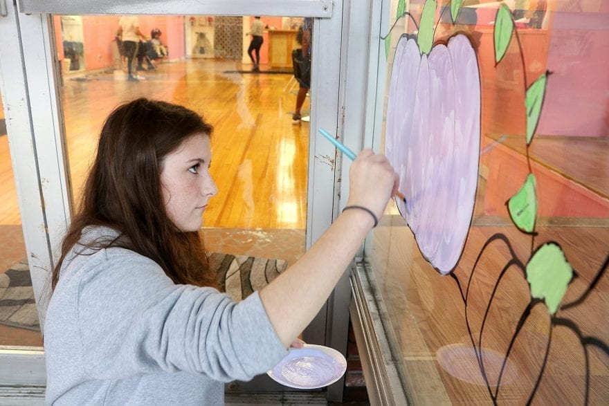 Brooke Hewett paints the storefront window Wednesday.