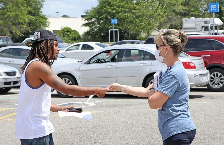 Stephanie Miller of Columbus Regional Healthcare System hands out a flyer in the Whiteville Walmart parking lot Wednesday.