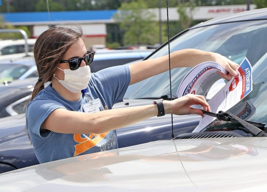 Mallory Freeman of Columbus Regional Healthcare System leaves a flyer on a car in the Walmart parking lot.