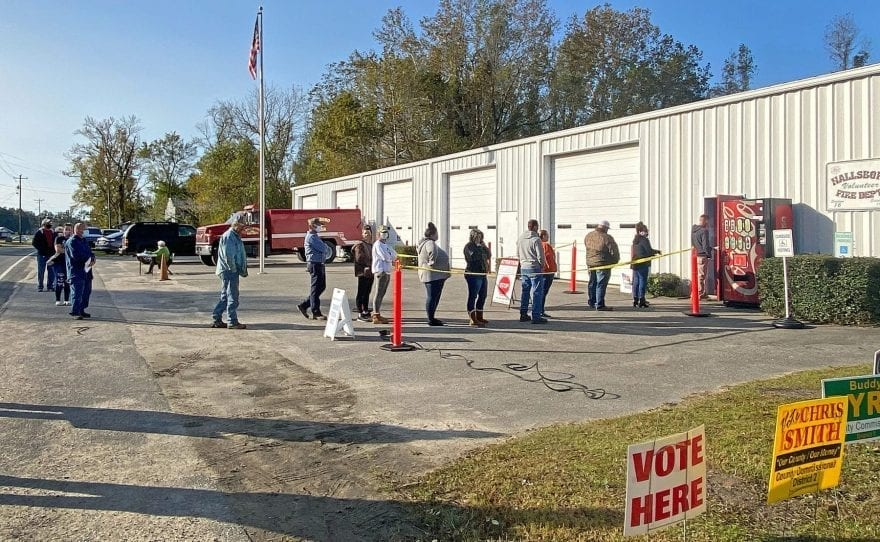 Voters wait in line outside the Hallsboro Volunteer Fire Department Tuesday morning to cast their ballots. Staff photo by Stuart Rogers