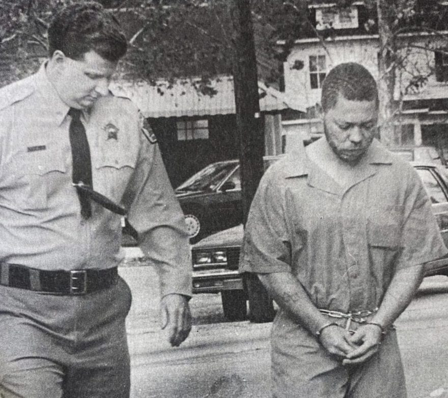 """Norfolk """"Fuzzy"""" Best is pictured on Dec. 13, 1991 being led into court for a first appearance after being charged with murder, rape, robbery and burglary."""