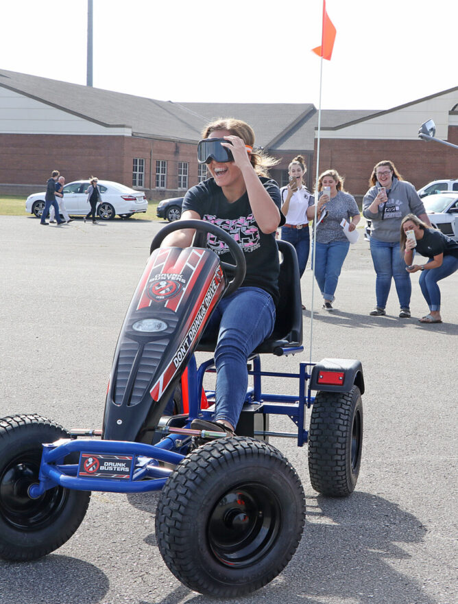 """A student takes a spin in a Columbus County Sheriff's Office """"Drunk Busters"""" pedal kart while wearing goggles meant to simulate impared driving."""