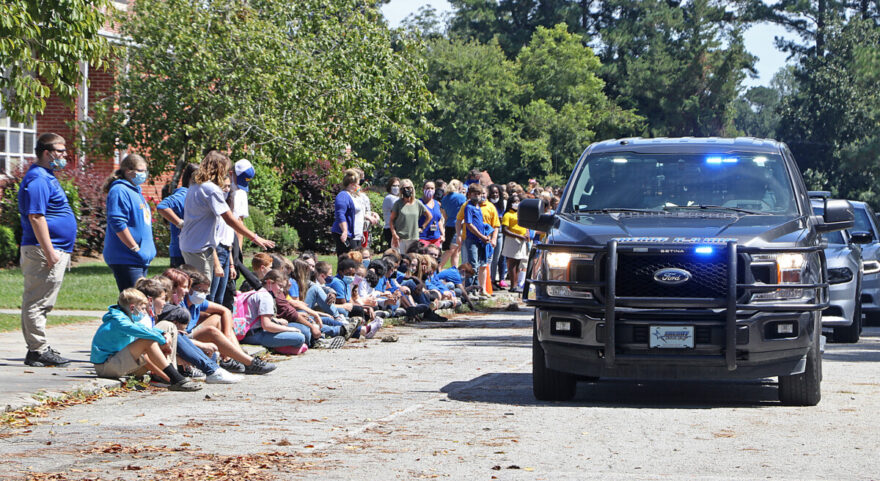 Students gather on the sidewalk as deputies from Columbus County Sheriff's Office drive past.